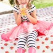 Stock Photo: Young Girl Wearing Pink Wellington Boots Drinking Orange Juice