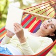 Stock Photo: WomRelaxing In Hammock With E-Book