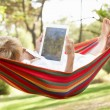 Senior Woman Relaxing In Hammock With  E-Book — Стоковая фотография