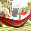 Senior Woman Relaxing In Hammock With  E-Book — Stockfoto