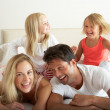 Family Relaxing Together In Bed - Lizenzfreies Foto