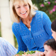 Senior Woman Serving At Multi Generation Family Meal — Stock Photo