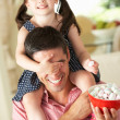 Stock Photo: Father Giving Daughter Ride On Shoulders Indoors Whilst Eating M