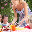 Mother Serving Birthday Cake To Group Of Children Outdoors - Foto Stock