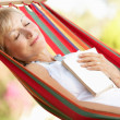 Senior Woman Relaxing In Hammock - Stockfoto