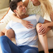 Couple Relaxing On Sofa At Home - Foto Stock