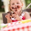 Stock Photo: Messy Girl Eating Chocolate Cake