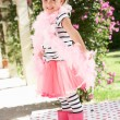 Stock Photo: Young Girl Wearing Pink Wellington And Feather Boa