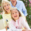 Grandparents Pushing Granddaughter In Wheelbarrow Filled With Or — Stock Photo #24639045