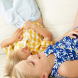 Two Children Lying Upside Down On Sofa At Home - Stock Photo