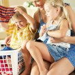 Mother And Children Sorting Laundry Sitting On Kitchen Counter - Stock Photo