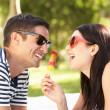 Stock Photo: Couple Relaxing Together In Garden Eating Ice Lolly
