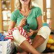 Senior Woman Sorting Laundry In Kitchen - Stock Photo