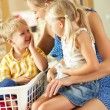 Mother And Children Sorting Laundry Sitting On Kitchen Counter — Stock Photo #24639135