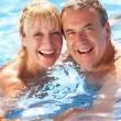 Senior Couple Having Fun In Swimming Pool — Stock Photo #24639221