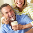 Senior Woman Feeding Husband Ice Cream — Stock Photo #24639355