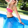 Stock Photo: WomWearing Bikini And Sarong By Swimming Pool