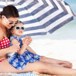 Mother And Daughter Under Beach Umbrella Putting On Sun Cream — Stock Photo