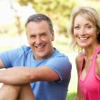 Senior Couple Resting After Exercising In Park — Stock Photo