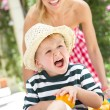 Mother Pushing Son In Wheelbarrow Filled With Oranges — Stock Photo #24639463