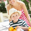 Stock Photo: Mother Pushing Son In Wheelbarrow Filled With Oranges