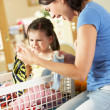 Mother And Daughter Sorting Laundry Sitting On Kitchen Counter — Stock Photo