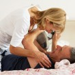 Senior Couple Fooling Around Together In Bed Whilst Man Reads Newspaper - Foto de Stock