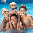Family Having Fun In Swimming Pool - Stock fotografie