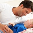 Father And Son Relaxing Together In Bed — Stock Photo