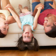 Family Lying Upside Down On Sofa With Daughter — Stock Photo #24639653