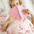 Senior Woman Relaxing In Bed Reading Diary - Foto Stock