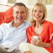 Senior Couple Relaxing On Sofa At Home Reading Newspaper — Stock Photo #24639711