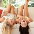 Stock Photo: Two Female Friends Lying Upside Down On Sofa