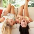 zwei Freundinnen, die kopfüber auf Sofa liegend — Stockfoto #24639733