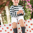 Stock Photo: Young Boy Wearing Wellington Boots Drinking Milkshake