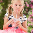 Stock Photo: Young Girl Wearing Pink Wellington Boots Drinking Milkshake