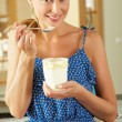 Woman Sitting On Kitchen Counter Eating Ice Cream — Stock Photo