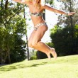 Woman Wearing Bikini Jumping In Garden — Stock Photo