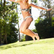 Stock Photo: Woman Wearing Bikini Jumping In Garden