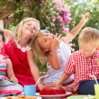 Group Of Children Eating Jelly At Outdoor Tea Party — Stock Photo #24639925