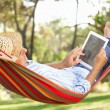 Senior Man Relaxing In Hammock With E-Book — Stock Photo