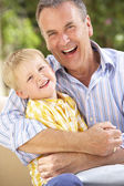 Grandfather And Grandson Relaxing On Sofa Together — Stock Photo