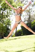 Mulher vestindo biquini pulando no jardim — Foto Stock