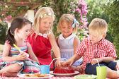 Gruppo di bambini mangiare gelatina al partito di tè all'aperto — Foto Stock