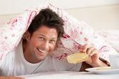 Man Snuggled Under Duvet Eating Breakfast — Stock Photo