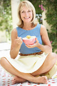 Senior Woman Enjoying Bowl Of Breakfast Cereal — Stock Photo