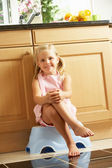 Girl Sitting On Plastic Step In Kitchen — Stock Photo