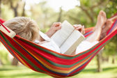 Senior Woman Relaxing In Hammock With Book — Stock Photo
