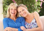 Mulher sênior com filha adulta relaxando no sofá em casa — Foto Stock