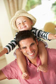 Father Giving Son Ride On Shoulders Indoors — Stock Photo
